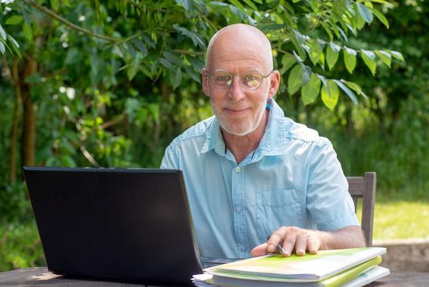 Hogere mens die laptop in de tuin met behulp van