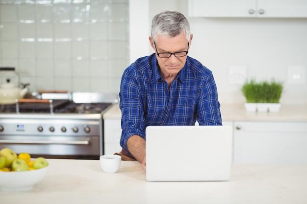 Hogere mens die laptop in keuken met behulp van