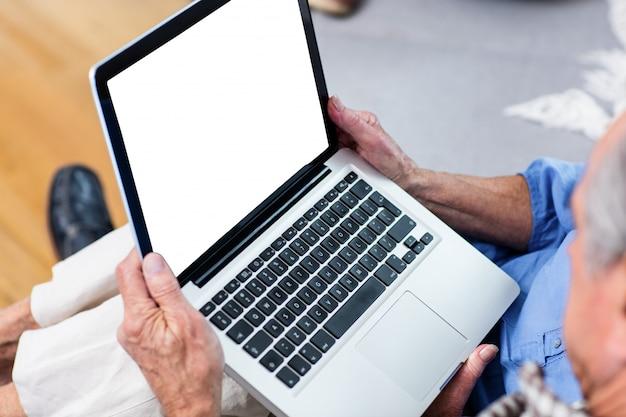 Hogere mens die laptop in woonkamer met behulp van
