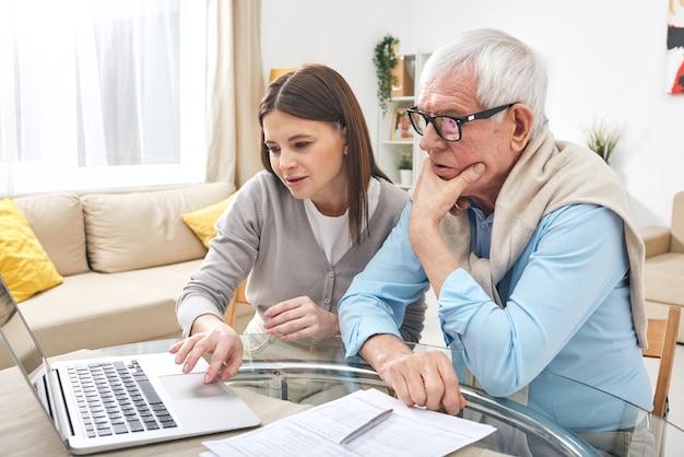 Hogere mens die laptopvertoning bekijkt terwijl zijn dochter hem uitlegt hoe om informatie in het net te zoeken