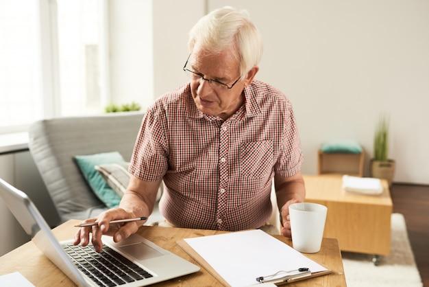 Hogere mens die met laptop thuis werkt
