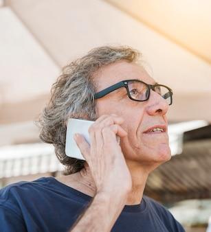 Hogere mens die oogglazen draagt die op smartphone spreken