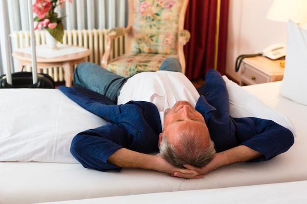Hogere mens die op het bed in de hotelruimte ligt