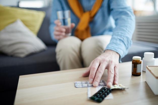 Hogere mens die pillenclose-up nemen