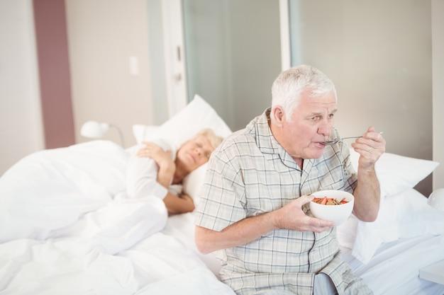 Hogere mens die salade eet door vrouw te slapen