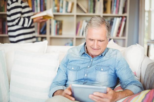 Hogere mens die tablet gebruikt terwijl het zitten op bank