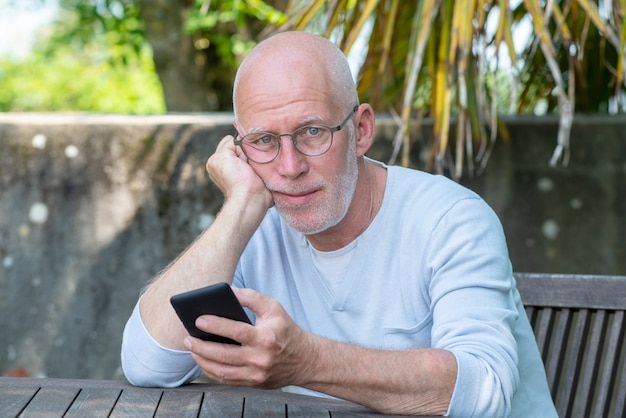Hogere mens die telefoon in de tuin met behulp van