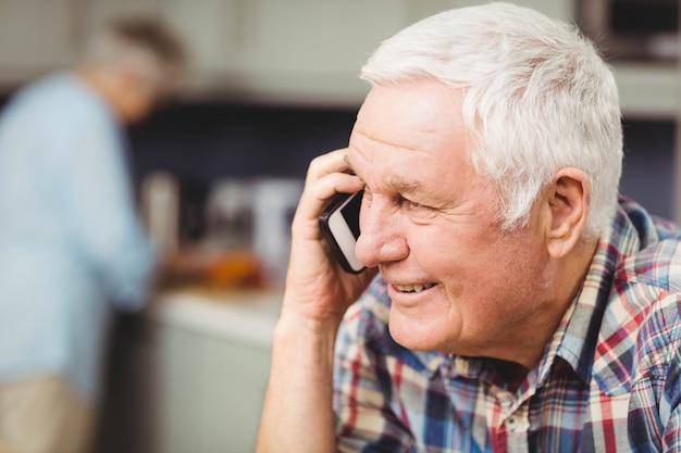 Hogere mens die terwijl het spreken op telefoon glimlacht