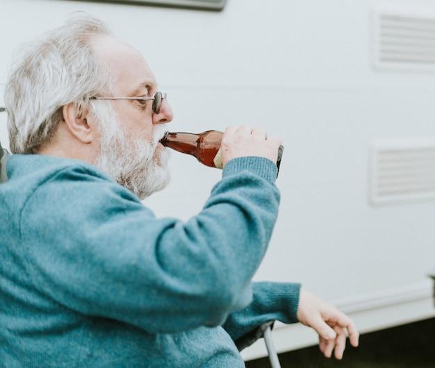 Hogere mens die van een fles bier geniet