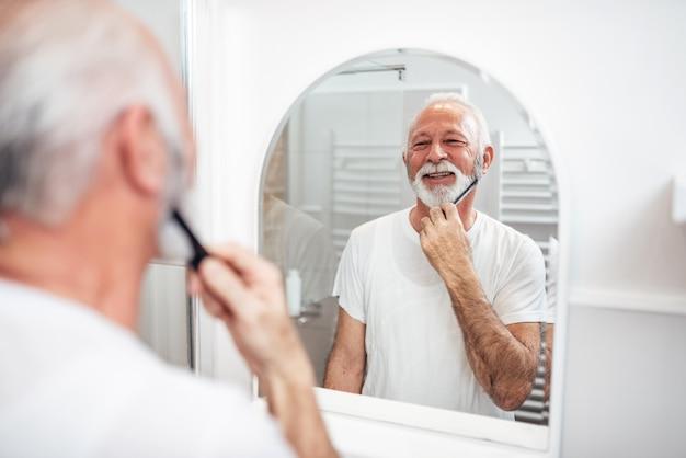 Hogere mens die zijn baard borstelt.