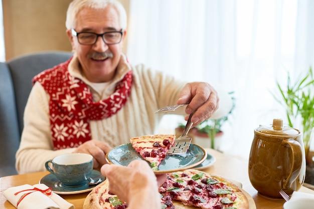 Hogere mens die zoete pastei eten bij kerstmisdiner