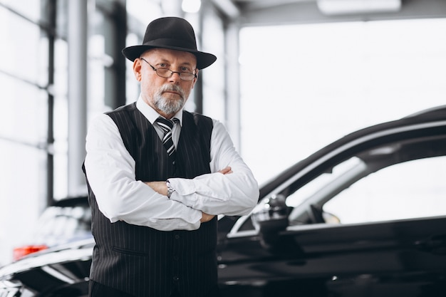 Hogere mens in een autotoonzaal die een auto kiest