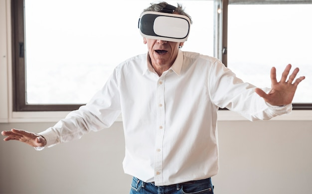 Hogere mens in wit overhemd die een virtuele werkelijkheidshoofdtelefoon in de ruimte met behulp van