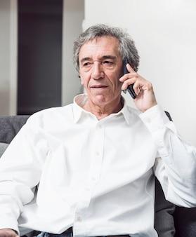 Hogere mens in wit overhemd die op mobiele telefoon spreken