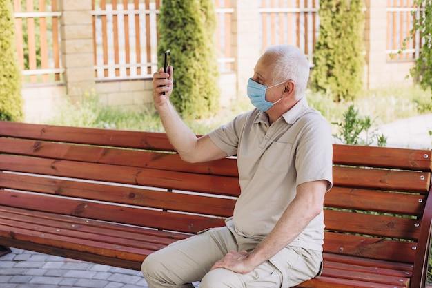 Hogere mens met medisch gezichtsmasker die de telefoon met behulp van om nieuws te zoeken en met familie te spreken