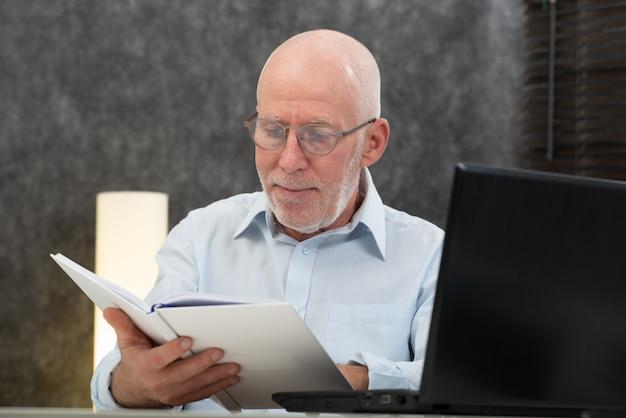 Hogere mens met witte haren en glazen die boek lezen