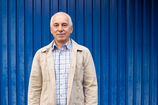 Hogere mens op blauwe achtergrond, copyspace. senior zakenman zelfverzekerd.