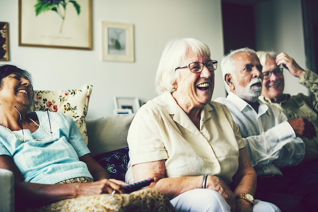 Hogere mensen die op televisie in de woonkamer letten
