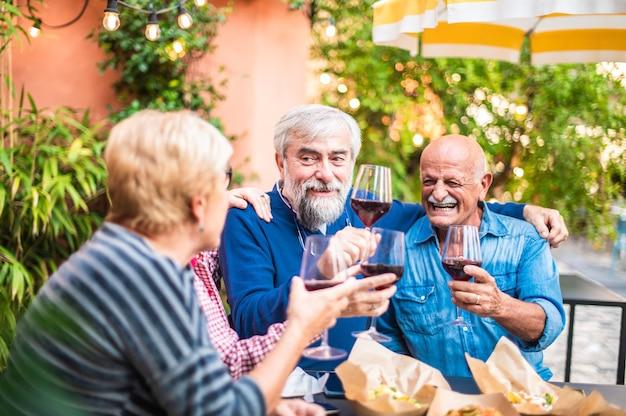 Hogere mensen die wijn roosteren bij restaurantbar