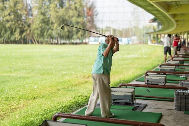 Hogere mensenoefening die zijn golfschommeling uitoefenen bij golf driving range.