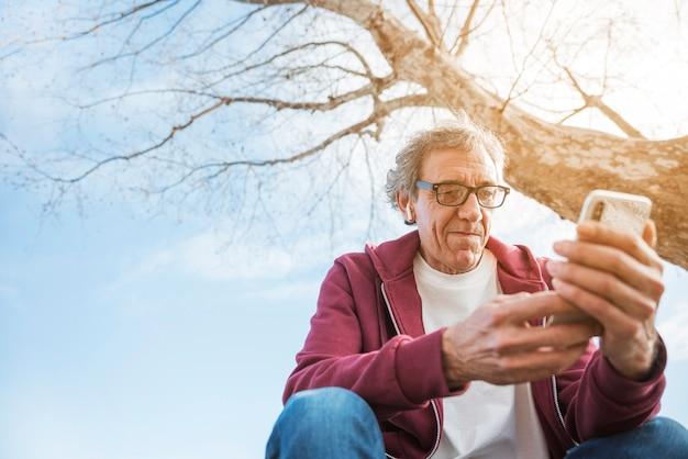 Hogere mensenzitting onder de boom die mobiele telefoon met bluetoothoortelefoon op zijn oren met behulp van