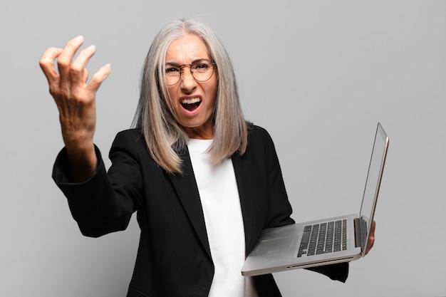 Hogere mooie onderneemster met laptop