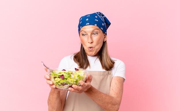 Hogere mooie vrouw die een salade voorbereidt