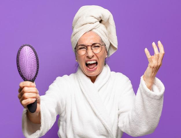 Hogere mooie vrouw met een haarborstel
