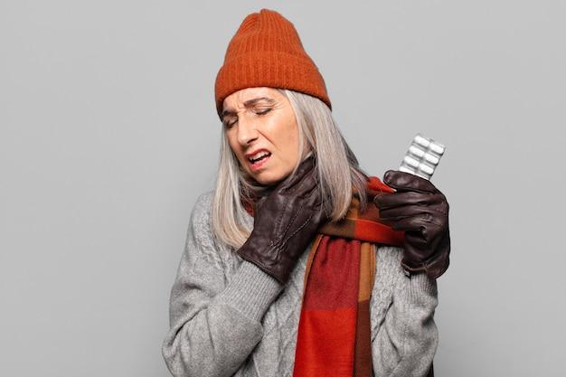 Hogere mooie vrouw met een pillen-tablet die de winterkleren draagt. griep concept