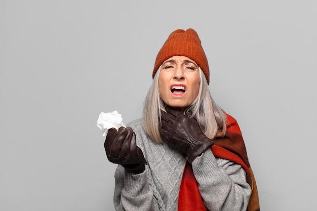 Hogere mooie vrouw met een pillen-tablet die de winterkleren draagt