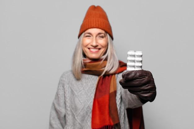 Hogere mooie vrouw met een pillentablet die winterkleren draagt. griep concept