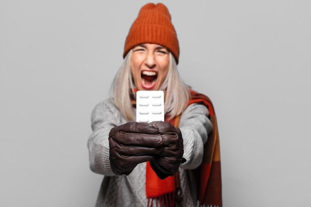 Hogere mooie vrouw met een pillentablet die winterkleren draagt.