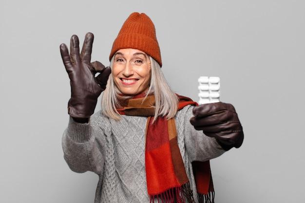 Hogere mooie vrouw met een pillentablet die winterkleren draagt