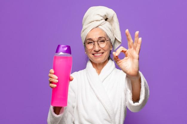 Hogere mooie vrouw na douche die badjas draagt. gezichtsreiniging of doucheproducten concept