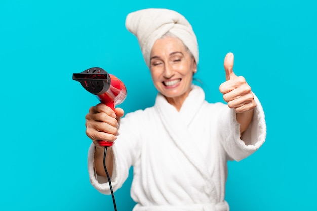Hogere mooie vrouw na douche die badjas draagt. haardroger concept
