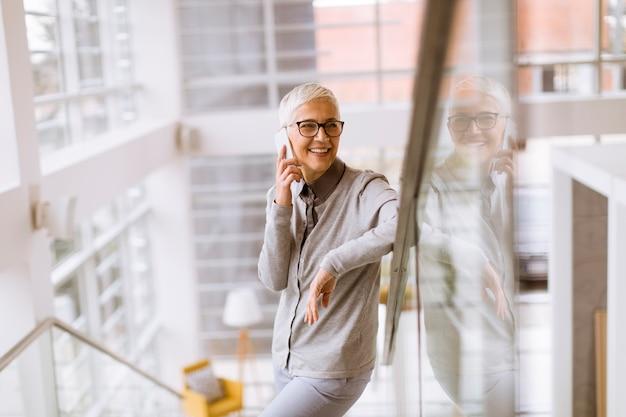 Hogere onderneemster die mobiele telefoon in modern ofice met behulp van