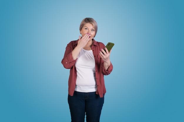 Hogere onderneemster met blond haar gebaren verbazing die haar mond bedekken met palm die een telefoon houdt en op blauwe muur stelt