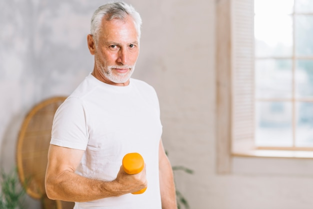 Hogere oudere mens het opheffen gewichten tijdens de zitting van de gymnastiektraining