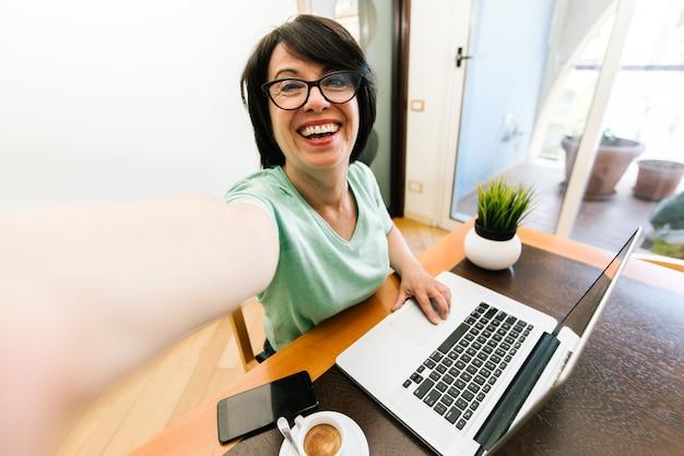 Hogere oudere vrouw die een selfie nemen die met laptop computer thuis aan de lijst in de woonkamer werken. oude volwassen mensen en technologie.