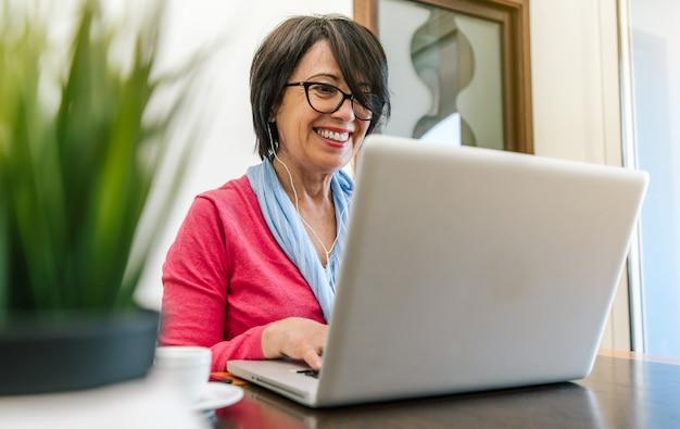 Hogere oudere vrouw die met laptop computer aan de lijst thuis binnen werkt. oude volwassen mensen en technologie concept