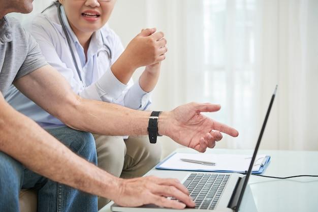 Hogere patiënt en arts die laptop met behulp van om geneeskundeprijzen op internet te controleren