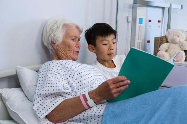 Hogere patiënt en jongen die een boek lezen