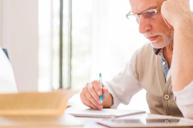 Hogere professor in glazen die op notitieboekje in klaslokaal schrijven