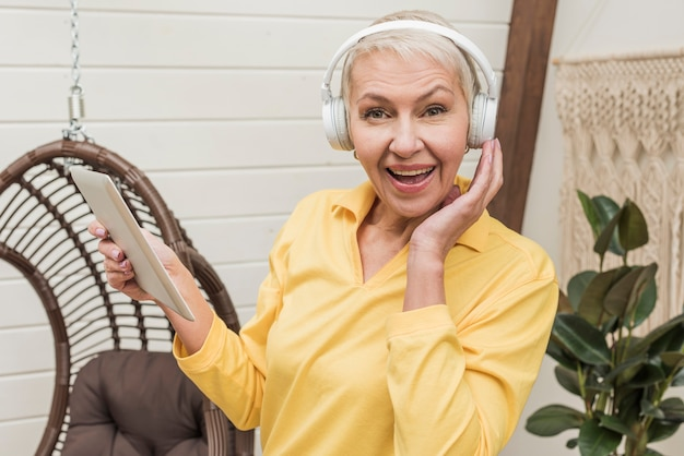 Hogere smileyvrouw die aan muziek hoewel hoofdtelefoons luistert