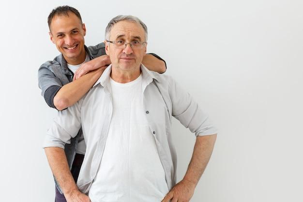 Hogere vader with adult son die op achtergrond wordt geïsoleerd