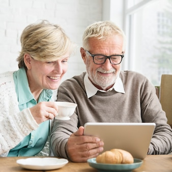 Hogere volwassene die het concept van de digitale apparatentablet gebruiken