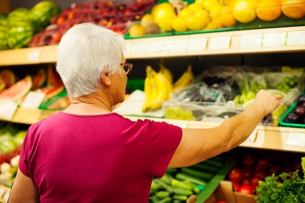 Hogere vrouw bij supermarkt