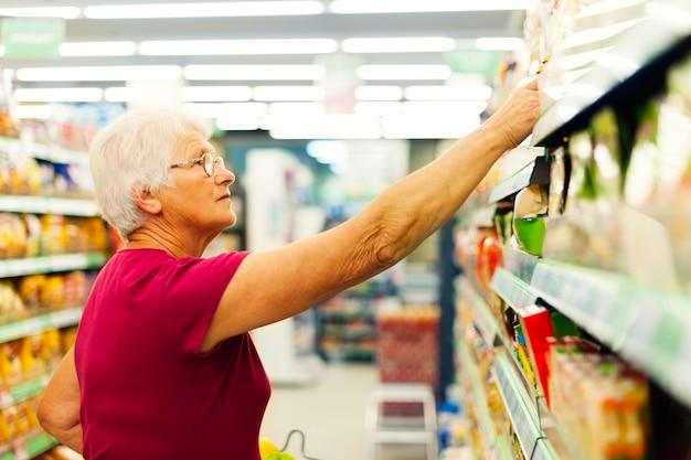 Hogere vrouw bij supermarkt Gratis Foto