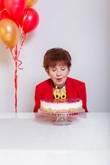 Hogere vrouw blazende kaarsen op cake