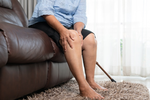 Hogere vrouw die aan kniepijn thuis lijden, gezondheidsprobleemconcept